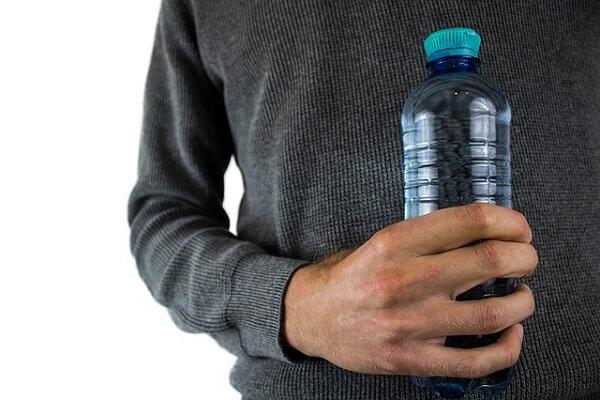 Hombre sostiene agua embotellada